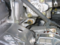 To remove a car alternator, first remove the adjustment bolt (center of the photo), then the bolt that connects the alternator to the engine block.